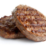 Two grilled hamburger patties isolated on white.